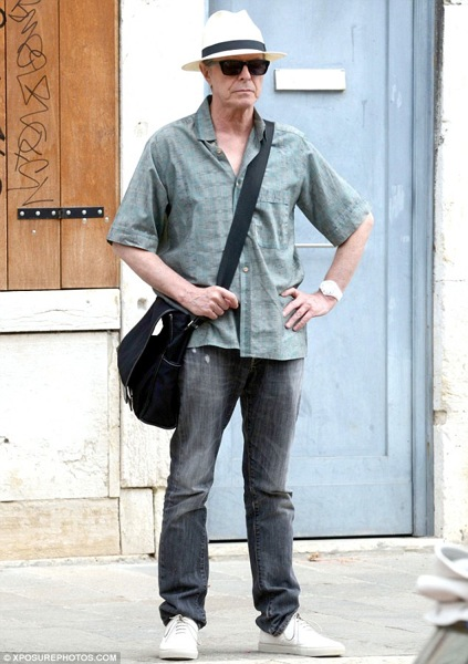 Bowie the holidaymaker: green button-down shirt, jeans, trainers, straw fedora, dark shades and man bag slung across his shoulder